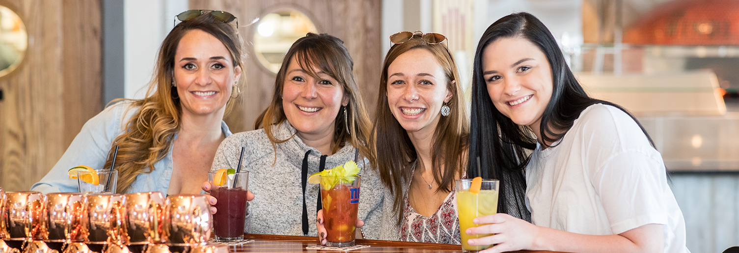 four young woman at The Windlass' bar posing for a picture with cocktail drinks in hand
