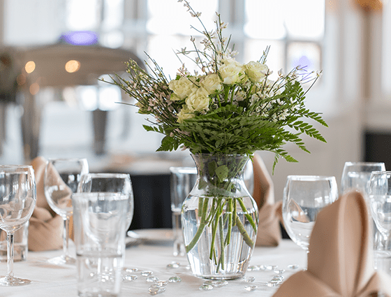 white flowers in a vase on a fully set table
